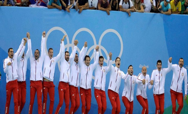 Members of the Serbia men\'s water polo team celebrate on the podium after winning their gold...