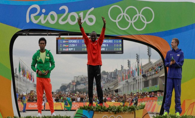 Kenya\'s Eliud Kipchoge, center, gold medal, celebrates on the podium flanked by silver medal...