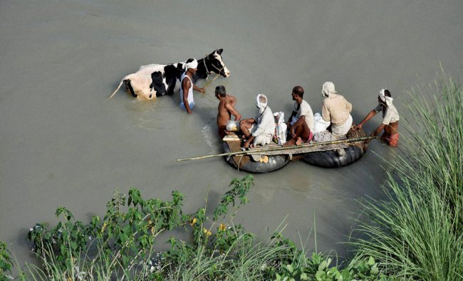 Villagers use tube boats to wade through flooded area of Hajipur, Bihar...