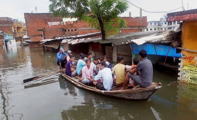 People on boat, wade through the flooded streets in Allahabad...