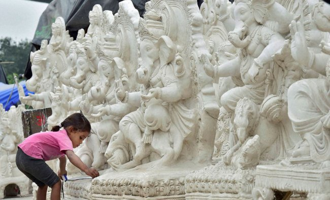 A child plays in front of idols of Lord Ganesha ahead of Ganesh festival ...