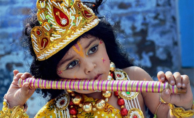 A child dresses as lord Krishna for a school function ahead of Janmashtami, in Bikaner...