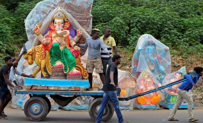 Workers transport an idol of Hindu god Ganesh on a cart ahead of the Ganesh Chaturthi festival...