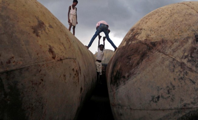 Children play on pontoons as clouds gather over the banks of the river Ganga in Allahabad...