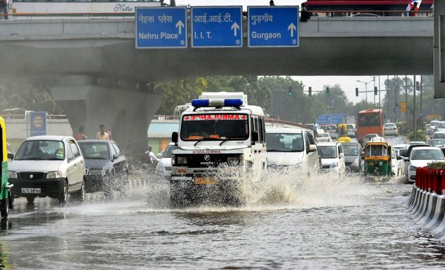 An Ambulance passes through a water logged road near AIIMS hospital after rains in New Delhi...