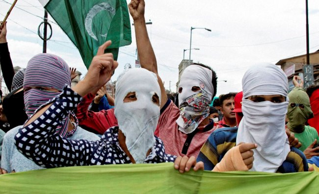 Masked protesters shout slogans at a protest march during a strike, after curfew was completely...