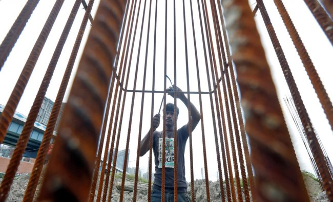 A labourer works at the construction site of a metro rail station in Kolkata...