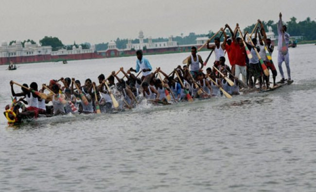 Oarsmen rows serpentine boat unisonly during annual boat race festival at Rudrasagar lake...