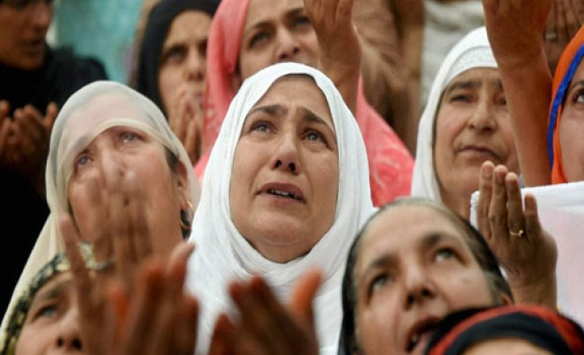 Devotees pray as head priest (not in picture) displays a holy relic of Prophet Muhammad...