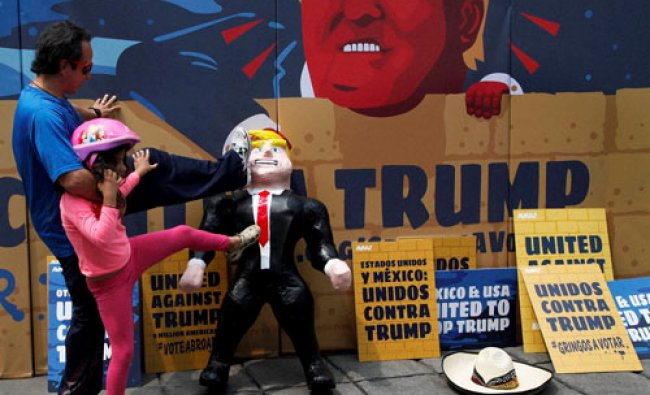 A girl and her father kick a pinata representing Donald Trump...