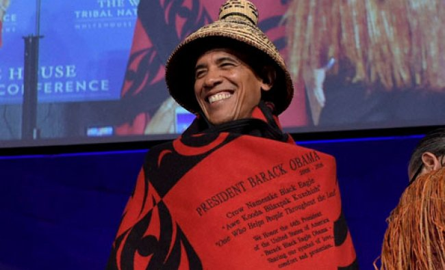 President Barack Obama smiles as he wears a blanket that was presented to him....