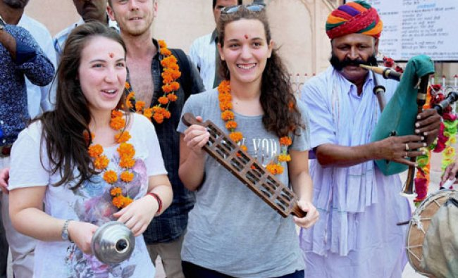 Foreign tourists enjoy with the folk artists at Junagarh Fort on the World Tourism Day...