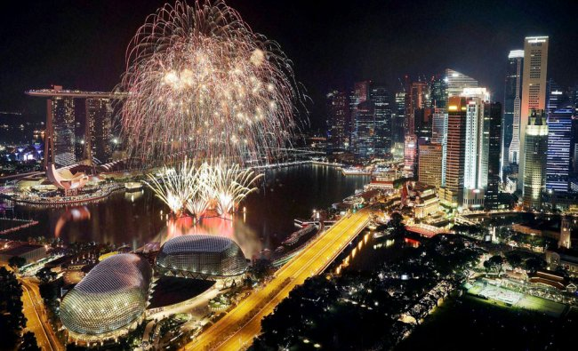 Fireworks explode above Singapore\'s financial district at the stroke of midnight to mark...