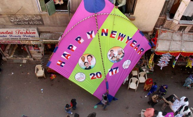 People hang huge kite on the eve of New Year at a Kite market in Ahmedabad...