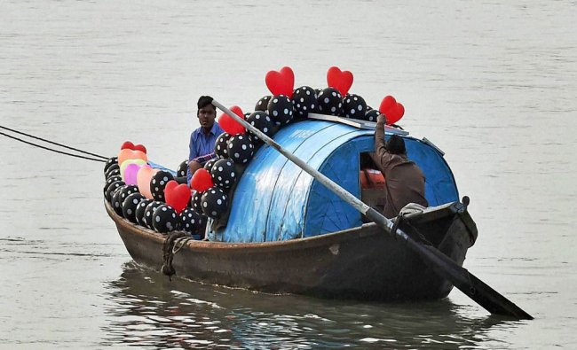 Boatsman decorates his boat with colorful balloons to attract people for boat ride...