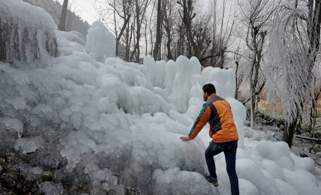 , J&K: A man tries to climb huge icicles at Kokarnag in Anantnag District of South Kashmir on...