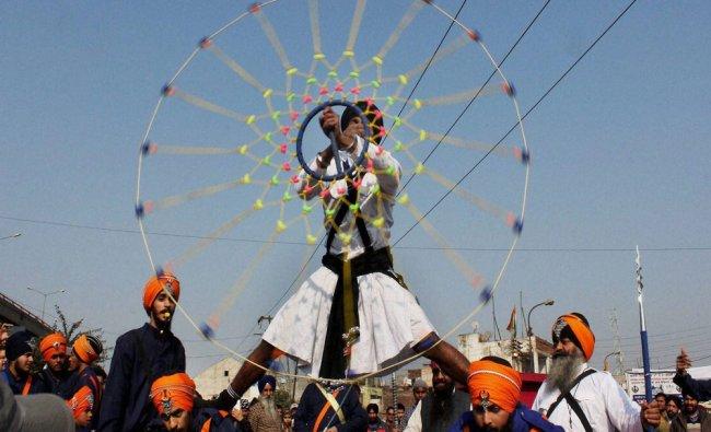 Sikh devotees perform marshal arts during the Nagar Kirtan (Procession) to celebrate 350th birth...