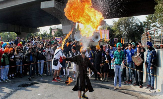 A Sikh devotee blows fire during the Nagar Kirtan (Procession) to celebrate 350th birth...