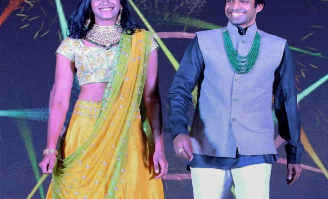 Shuttler PV Sindhu and coach P Gopichand walk the ramp during the Opening Ceremony of the...
