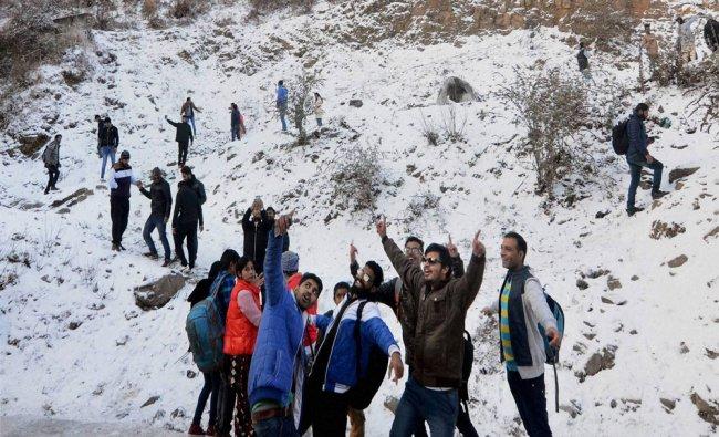 Tourists click selfies amid fresh snowfall in Kufri near Shimla on Monday...