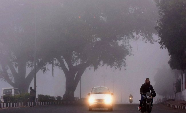 Vehicles move amidst a thick blanket of fog in Bhopal on Monday...