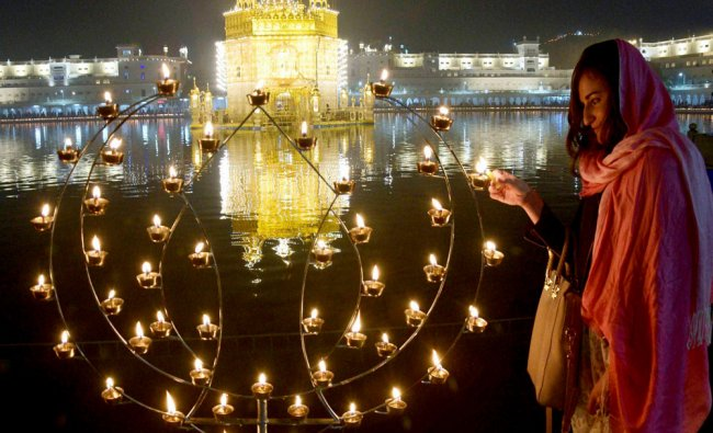 A foreigner lights up candles at the illuminated Golden Temple on the occasion of the 350th...