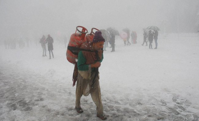 A Kashmiri laborer carries gas cylinders on his back as he walks on the snowy road following...
