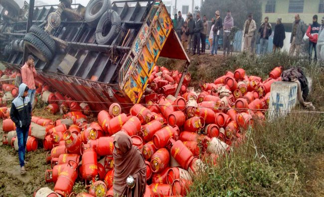 A truck overloaded with gas cylinders turns turtle following a road accident on a foggy...