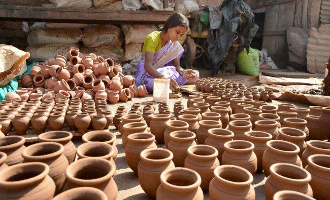 A woman makes clay pots ahead of the Makar Sankrati festival, in Karad, Maharashtra...