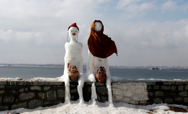 A snow man and a snow woman with \'Kangris\', traditional fire pots, are installed on the banks...