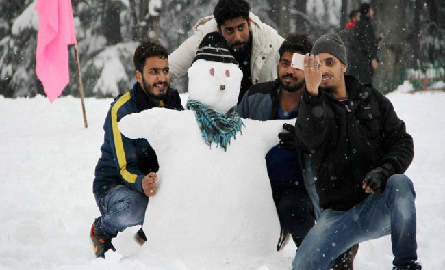 Tourists click selfies with a snowman at agorund in Patnitop near Jammu...