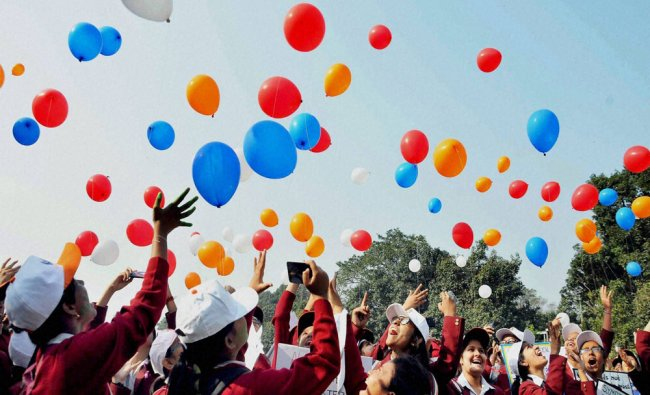 School girls flying colourful balloons as they participate in an awareness rally...