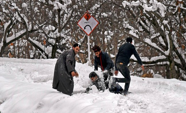 Boys playing with snow after heavy snowfall on the outskirts of Srinagar on Monday...