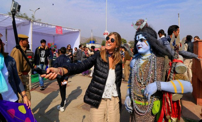 Foreign tourists pose for photos with artists in costume during the Kite Festival, at Jal Mahal...