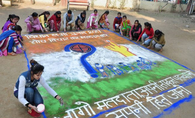 Students make a rangoli to aware people on voting in Moradabad on Sunday...