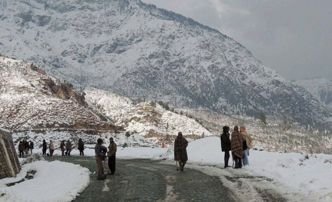 People walk on a snow covered road following heavy snowfall at Kandi Area in Budhal, Rajouri...
