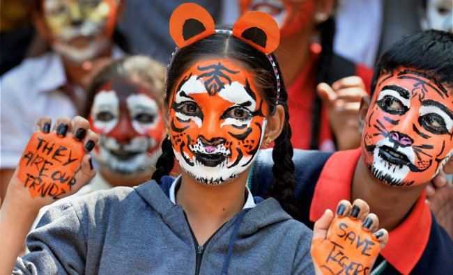 Students paint their faces as tiger during a tiger programme for Inter-school Tiger Fest...