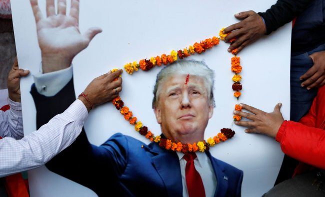 Members of Hindu Sena, a right-wing Hindu group, place a garland on an poster...