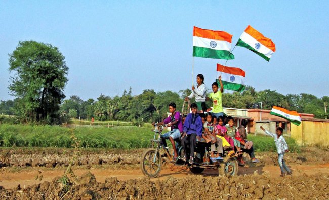 Children holding national flags as they ride on a modified motorcycle ahead of the Republic...
