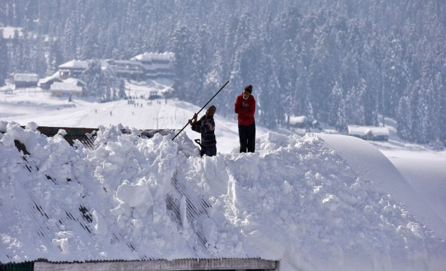 A worker removes snow from the roof of a hotel on a sunny day in Gulmarg, west of Srinagar...