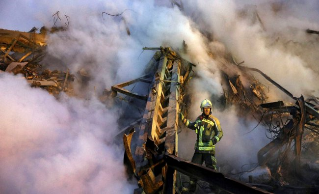 An Iranian firefighter removes debris of the Plasco building which was engulfed by a fire...