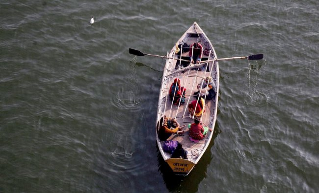 A boat man carries Hindu devotees in the river Yamuna early in the morning during magh Mela in...