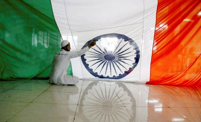 A worker stitches the national flag at a workshop on the occasion of Republic Day in Bhiwandi...
