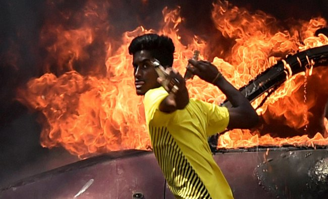 A pro-Jallikattu protester throwing bottles at police personnel during a clash near Marina...