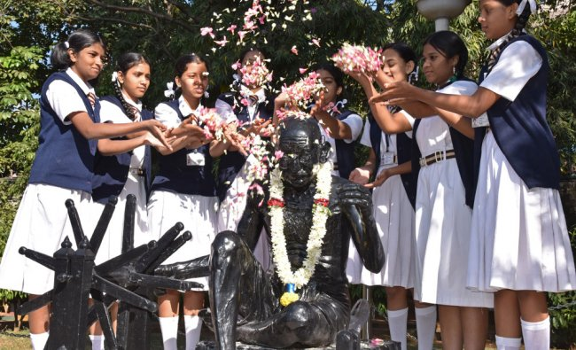 Children shower flowers on Mahatma Gandhi\'s statue....