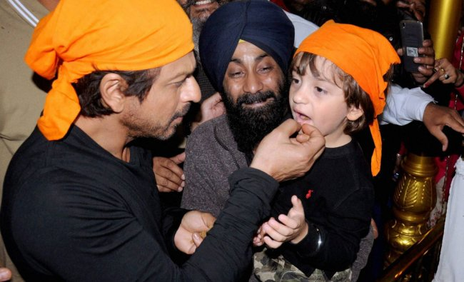 Bollywood Actor Shah Rukh Khan giving \'parshad\' to his son while paying obeisance at Golden temple