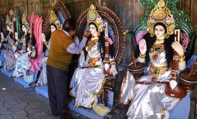 An artist giving final touches to an idol of Goddess Saraswati on the eve of Basant Panchami in ...