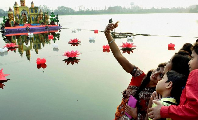 A girl taking selfie with children at Saraswati puja pandal on the Loco Tank in Dhanbad ...