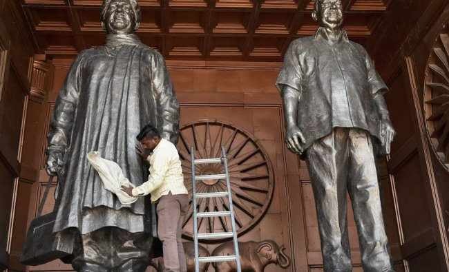 A worker cleans a statue of BSP chief Mayawati in Lucknow on Friday. The contractors have been...