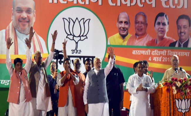 Prime Minister Narendra Modi waves during an election campaign rally in Varanasi ...